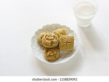 Homemade matcha green tea cookies on white table . glass of fresh milk.