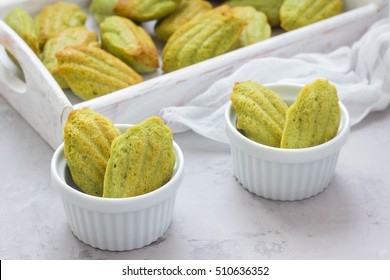 Homemade matcha green tea madeleines on the table and in wooden tray, horizontal