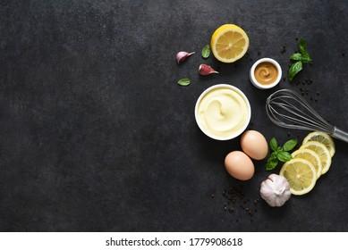 mayonnaise faite maison sur fond noir. Ingrédients pour faire la sauce: oeuf, beurre, moutarde.