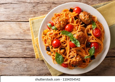 Homemade meat balls with spaghetti, aubergines and tomatoes close-up on a plate. horizontal top view from above