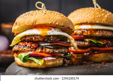 Homemade meat burgers with egg, sauce and vegetables on a dark background.