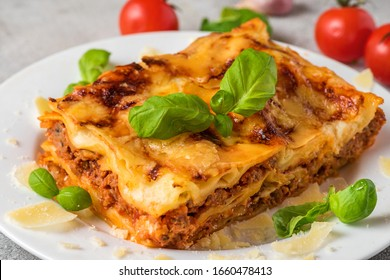 Homemade meat lasagna with fresh basil and parmesan cheese in a plate on white wooden table. close up. italian food.