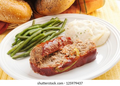 homemade meat loaf served with healthy green beans, mashed potatoes and kaiser rolls.