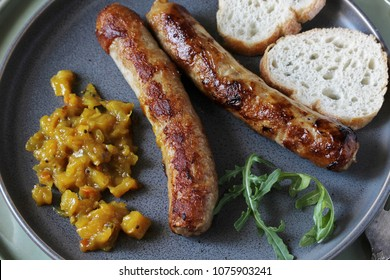 Homemade meat sausages with mango chutney sauce on a plate for concrete and gray concrete background. Modern hipster style.