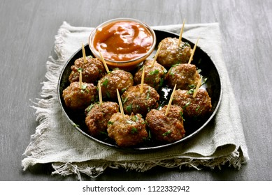 Homemade meatballs with tomato sauce on black stone table