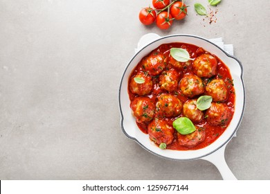 Homemade meatballs with tomato sauce and spices served in white pan on grey background. Top View with copy space.