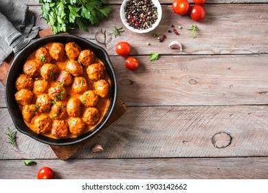 Homemade Meatballs in Tomato Sauce, top view, copy space. Beef meatballs in cast iron pan on wooden background.