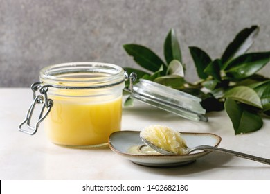 Homemade Melted ghee clarified butter in open glass jar and spoon on saucer standing on white marble table with green branch. Grey wall at background.