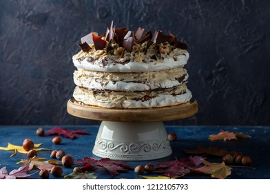 Homemade meringue cake with coffee cream, hazelnut and chocolate on a dark textured background with autumn leaves.
