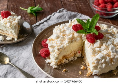 Homemade Meringue Ice Cream Cake with a slice cut out, decorated with raspberries and fresh mint leaves, on a rustic dark wooden background