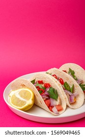 Homemade Mexican Tacos with fresh vegetables and chicken on fucshia background. Healthy food .Burritos. Isolated