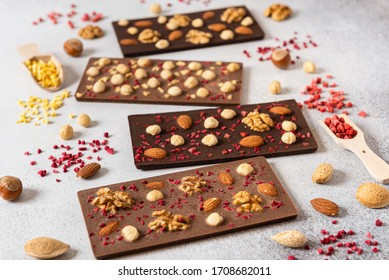 Homemade milk and dark chocolate bars with dried berries and nuts on light background. Side view. Chocolatier work, close up