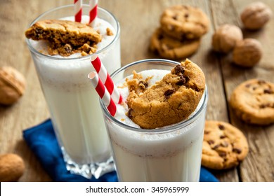 Homemade milkshake with chocolate chips cookies and nuts  on rustic wooden table close up