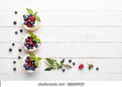 Homemade millefeuille with berries and fresh mint leaves, top view.