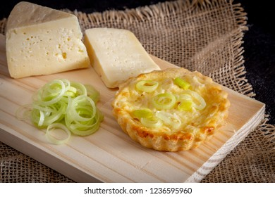 Homemade mini quiche with cheese and leek on rustic background.