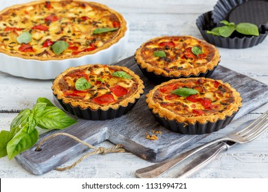 Homemade mini quiche with chicken, green onions and sweet pepper on an old wooden table.
