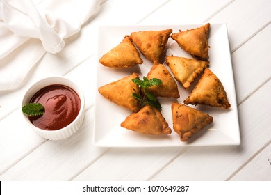 homemade mini samosa served with red sauce, selective focus