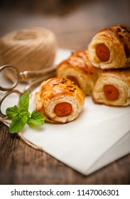 Homemade mini sausage pie baked in pastry on wooden background