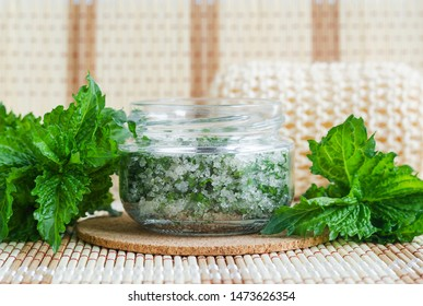 Homemade mint exfoliating scrub (foot soak, bath salt) with sugar, chopped mint leaves, olive oil end essential mint oil. Natural skin and hair care. DIY beauty treatments, spa recipe. Copy space.