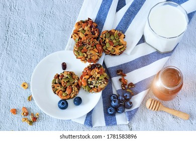 Homemade mixed cereal and fruit cookies with a glass of milk and honey bee on white background