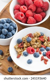 homemade muesli with fresh berries, nuts and yogurt for breakfast, top view, close-up, vertical