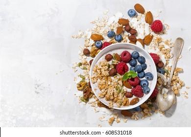 homemade muesli with yogurt and berries on white table, top view, horizontal