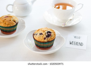 """Homemade muffin with blueberry and cup of tea and Text """"HELLO"""" WEEKEND."""