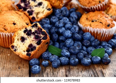 Homemade muffins with fresh blueberries on wooden table