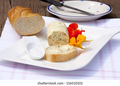 Homemade nasturtium herb butter on a plate with a piece of baguette and sea salt on a rustic wooden table