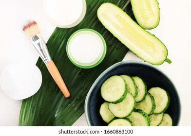 Hausgemachte natürliche Kosmetikprodukte mit Gurken für Schönheitsbehandlungen. Erfrischende Gesichtsmaske mit Kühlpflanzenextraktionsgel. Grüne Scheiben auf Blättern mit Hautpflegecreme-Wirkstoffen, Draufsicht, weißer Hintergrund