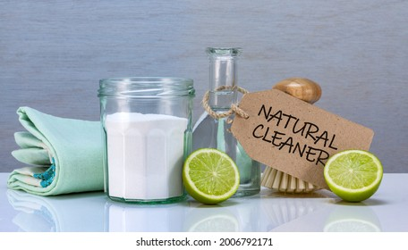 homemade natural eco cleaner with soda, vinegar and lime in recycled jars and bamboo made scrubbing brush, sustainable living