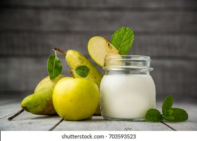 Homemade natural farmer yoghurt for breakfast in jar with fresh fruits - pears and apples on wooden desk, top view