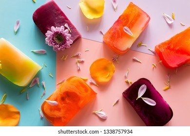 homemade natural soap, flowers and petals on a colored background