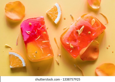 homemade natural soap on a yellow background with flower petals