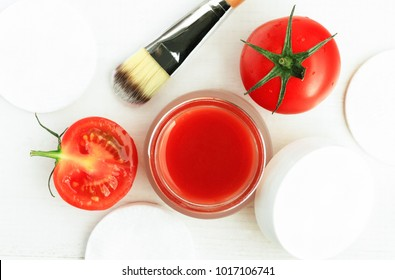 Homemade natural tomato cosmetic treatment. Facial mask in jar and fresh red vegetable slices, top view white wooden table.