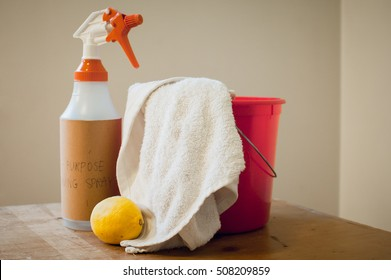 Homemade natural/green cleaning supplies- spray bottle, lemon, white rag, and red bucket on a wooden background