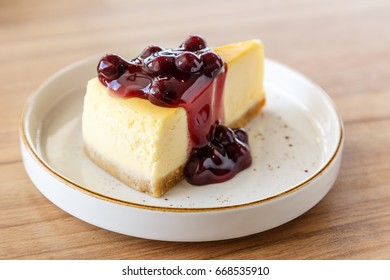 Homemade New York cheesecake with blueberry sauce on a wooden table