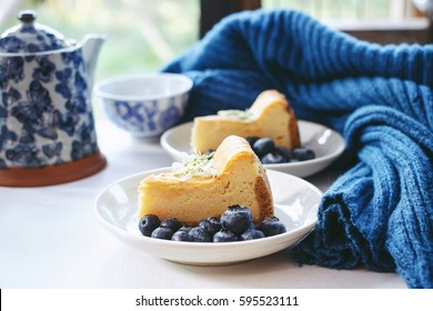 Homemade New York cheesecake with fresh blueberry, cozy blanket navy color and old tea pot, Breakfast set in holiday in winter. Hand moving in frame.