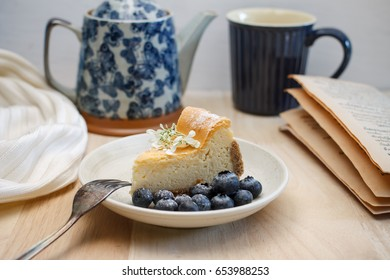 Homemade New York cheesecake with fresh blueberry, cozy blanket white color and old tea pot, Breakfast set in holiday in winter.