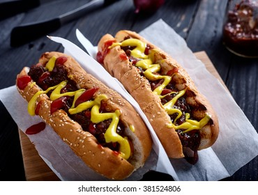 Homemade New York Style Hot dog. Sausage with sweet onion sauce, ketchup and mustard in white bun. wood background with onions, sauce and tongs on back