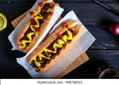 Homemade New York Style Hot Dog with Onion sauce. Dark wood background with onion and tongs on back