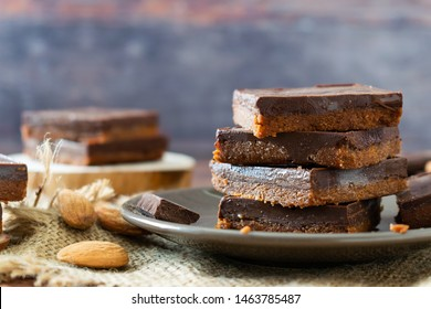 Homemade No Bake Paleo Chocolate Almond Butter Bars with almond butter, coconut flour, chocolate, maple syrup. Rustic background
