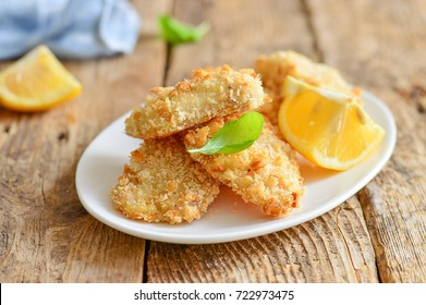 Homemade nuggets (fish, chicken) with a slice of lemon. A white plate. Wooden background. Horizontal photo of photo.