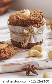 Homemade nutty vegan cinnamon cookies on white beige wooden board, close-up, natural light