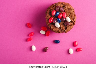 Homemade oat chocolate cookies stack with cereal with juicy jelly beans on minimal pink purple background, top view