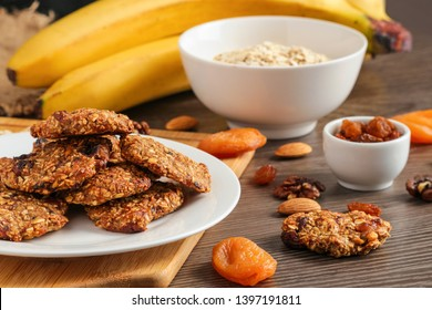 homemade oat cookies chips and ingredients banana walnuts almonds raisin dried apricots soft focus close up