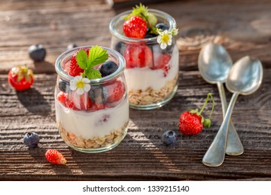 Homemade oat flakes with berries and yoghurt in jar