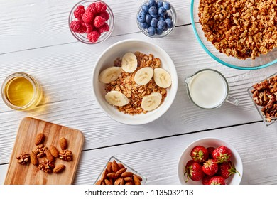 Homemade oat granola with bananas, nuts, berries and honey in glass bowl, milk in bottle on white wooden background. Copy space. Top view
