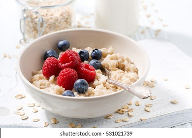 homemade oatmeal with berries on white wooden board, closeup, horizontal