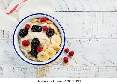 Homemade oatmeal for breakfast with banana, blackberry and raspberry on white wooden table